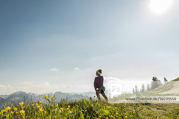 Austria  Tyrol  Tannheim Valley  young woman standing in mountainscape looking at view