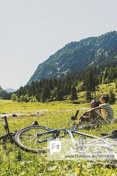 Österreich  Tirol  Tannheimer Tal  junges Paar mit Mountainbikes zum Entspannen auf der Wiese