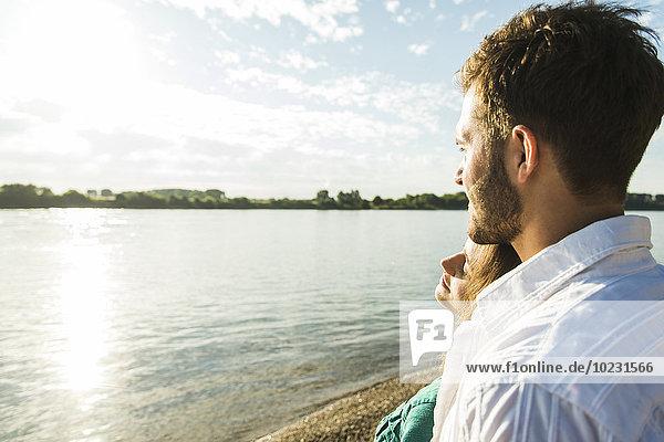 Junges Paar am Flussufer mit Blick auf die Aussicht