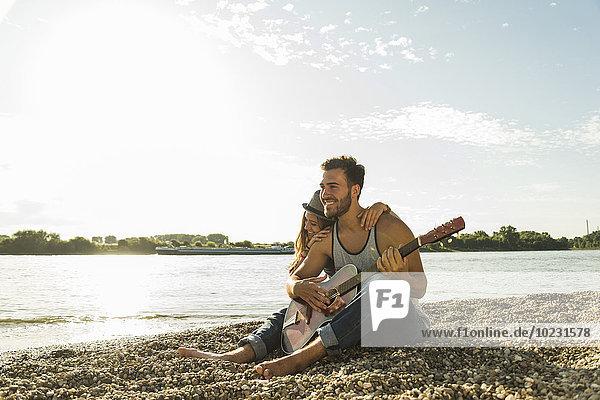 Glückliches junges Paar mit Gitarre am Flussufer