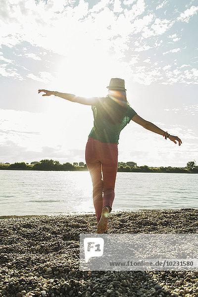 Junge Frau balanciert am Flussufer