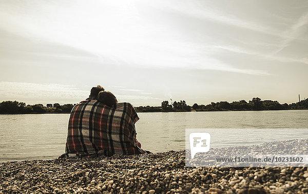 Junges Paar mit Decke am Flussufer sitzend