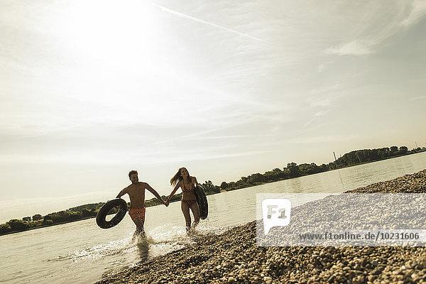 Junges Paar  das mit Innenrohren im Fluss läuft