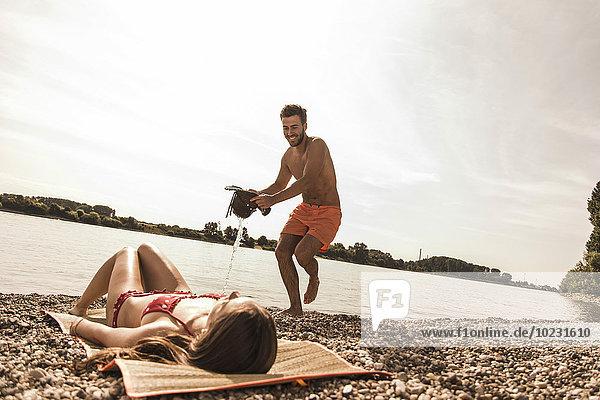 Verspielter junger Mann  der versucht  Wasser über die Freundin zu gießen  die sich am Flussufer sonnt.