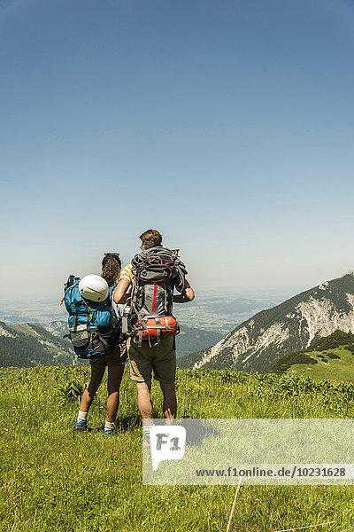 Österreich  Tirol  Tannheimer Tal  junges Paar auf der Alm stehend mit Blick auf die Aussicht