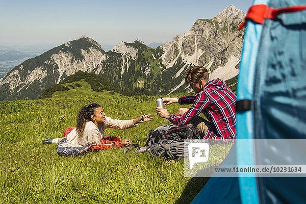 Österreich  Tirol  Tannheimer Tal  junges Paar ruht neben dem Zelt auf einer Almwiese