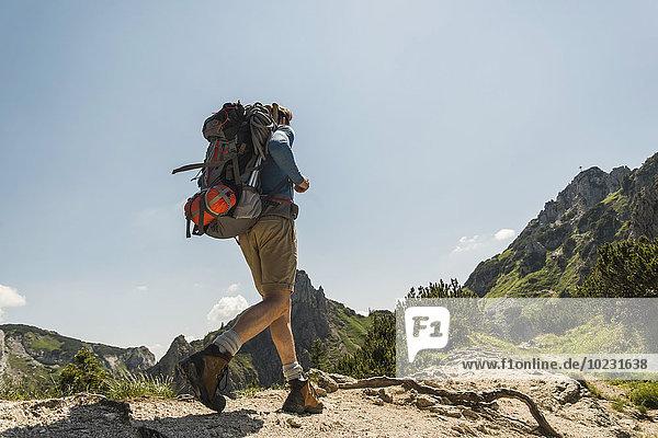 Austria  Tyrol  Tannheimer Tal  young man hiking on mountain trail