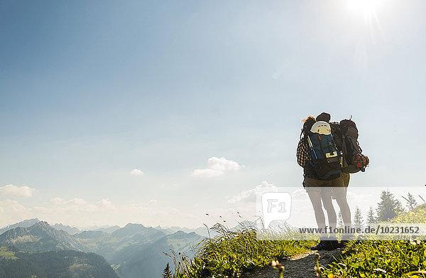 Österreich  Tirol  Tannheimer Tal  junges Paar auf dem Bergpfad stehend mit Blick auf die Aussicht