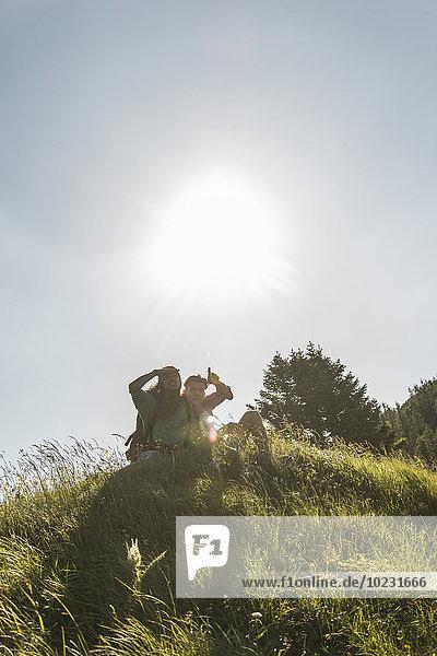 Österreich  Tirol  Tannheimer Tal  junges Paar auf der Alm sitzend mit Blick auf die Aussicht