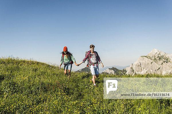Österreich  Tirol  Tannheimer Tal  junges Paar geht Hand in Hand auf der Alm