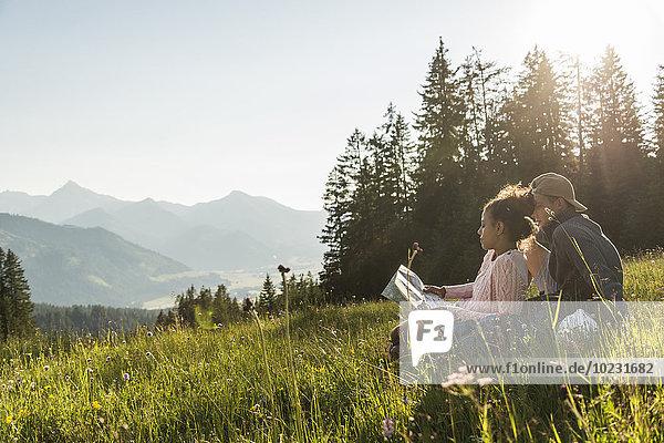 Österreich  Tirol  Tannheimer Tal  junges Pärchen auf der Alm mit Blick auf die Karte
