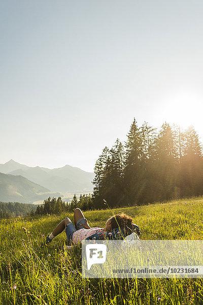 Österreich  Tirol  Tannheimer Tal  junge Frau auf Alpweide liegend