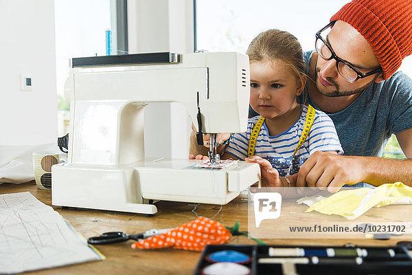 Vater und Tochter zu Hause mit der Nähmaschine