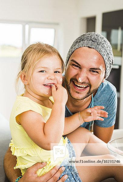 Glücklicher Vater und Tochter beim Backen in der Küche