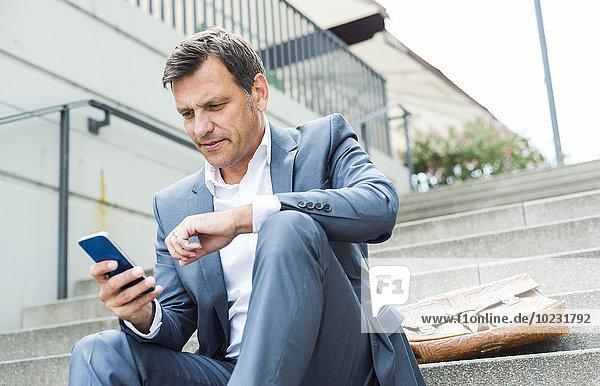 Geschäftsmann auf der Treppe sitzend mit Smartphone
