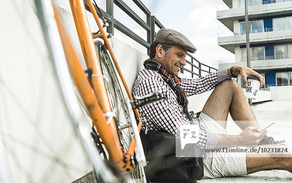 Mature man with bicycle leaning on wall  holding coffee cup and smart phone