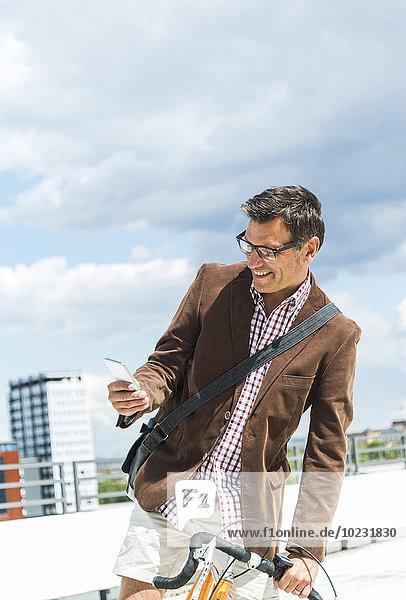 Erwachsener Mann mit Fahrrad über Smartphone