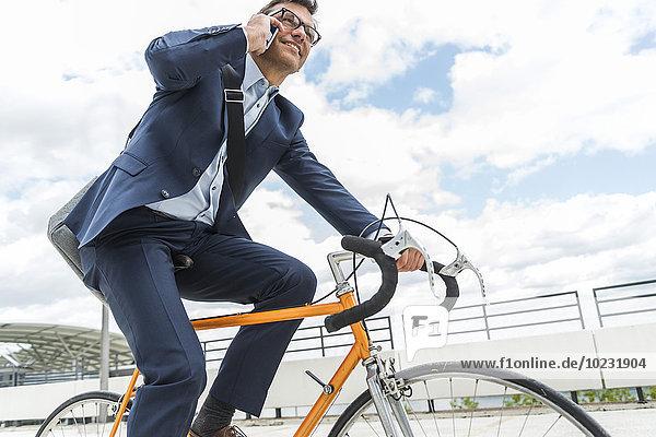 Geschäftsmann auf dem Fahrrad  telefonierend