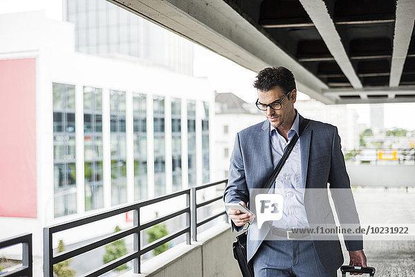 Geschäftsmann auf Geschäftsreise mit Blick auf sein Smartphone