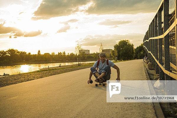 Mann sitzt auf dem Skateboard in der Abenddämmerung