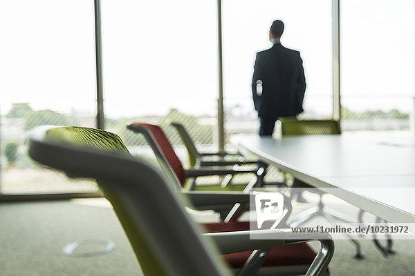 Konferenzraum mit Geschäftsmann am Fenster