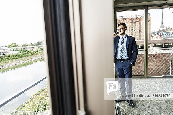 Junger Geschäftsmann mit Handy aus dem Fenster schauend