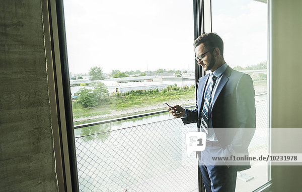 Junger Geschäftsmann am Fenster mit Blick aufs Handy