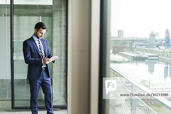 Junger Geschäftsmann am Fenster mit Blick auf das digitale Tablett