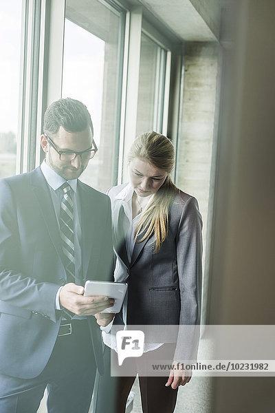 Junger Geschäftsmann und Geschäftsfrau am Fenster mit Blick auf digitales Tablett
