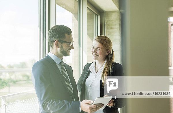 Lächelnder junger Geschäftsmann und Geschäftsfrau am Fenster mit digitalem Tablett