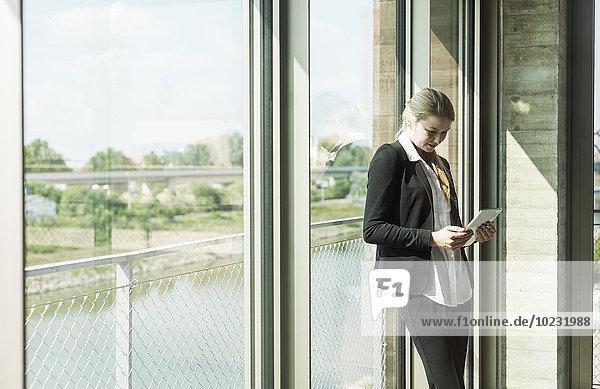 Junge Geschäftsfrau am Fenster mit Blick auf das digitale Tablett
