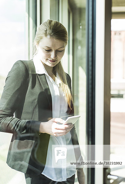 Smiling young businesswoman at the window looking on cell phone