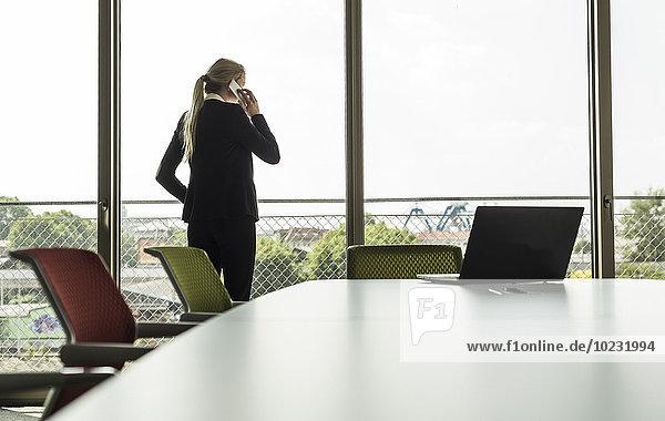 Junge Geschäftsfrau im Konferenzraum am Handy