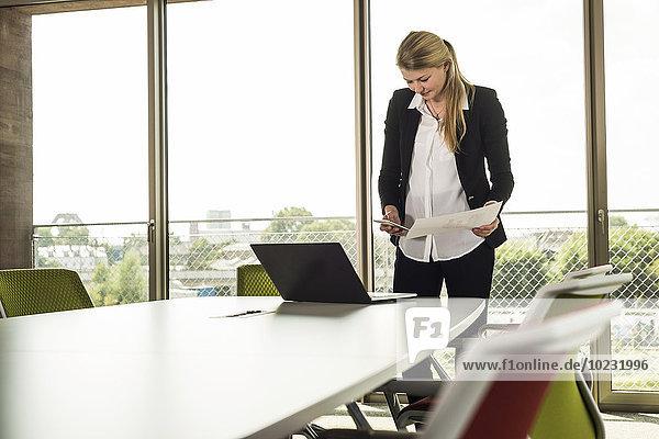 Junge Geschäftsfrau im Konferenzraum mit Handy  Laptop und Unterlagen