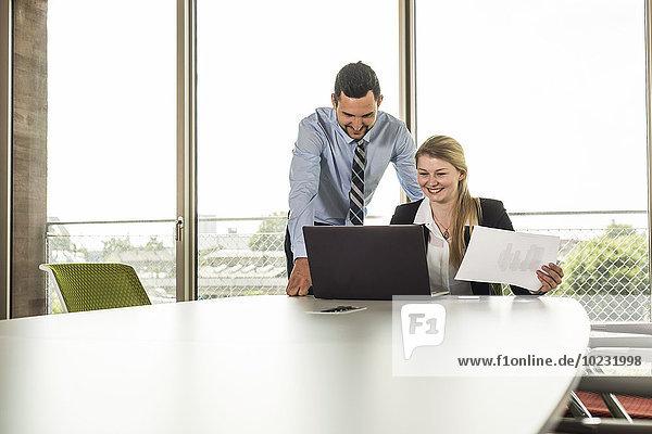 Lächelnder junger Geschäftsmann und Geschäftsfrau im Konferenzraum mit Laptop