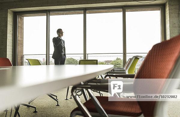 Konferenzraum mit Geschäftsmann am Telefon