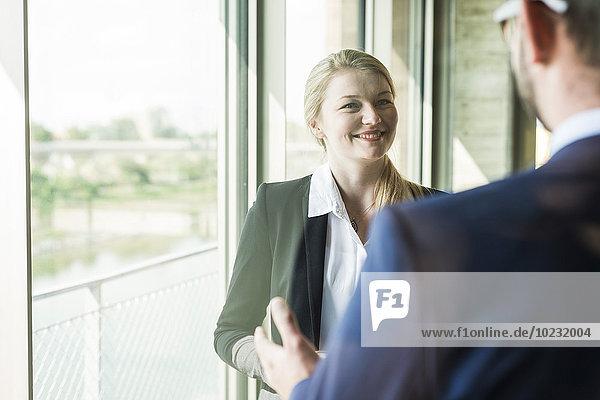 Lächelnde junge Geschäftsfrau am Fenster mit Blick auf Geschäftsmann