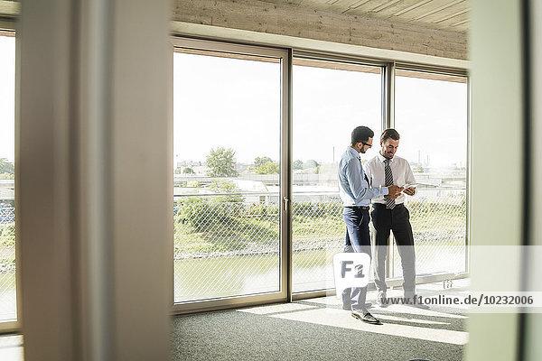 Zwei Geschäftsleute mit digitalem Tablett am Fenster