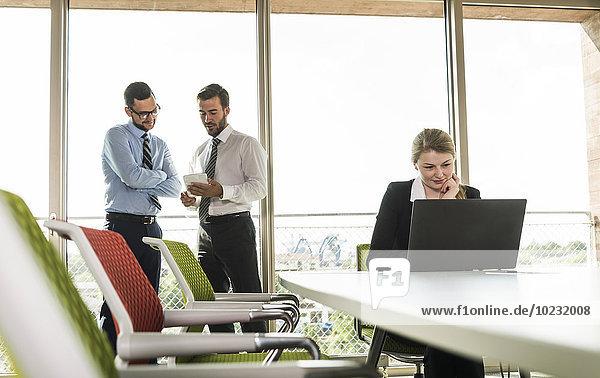 Zwei Geschäftsleute mit digitalem Tablett und Geschäftsfrau mit Laptop im Konferenzraum