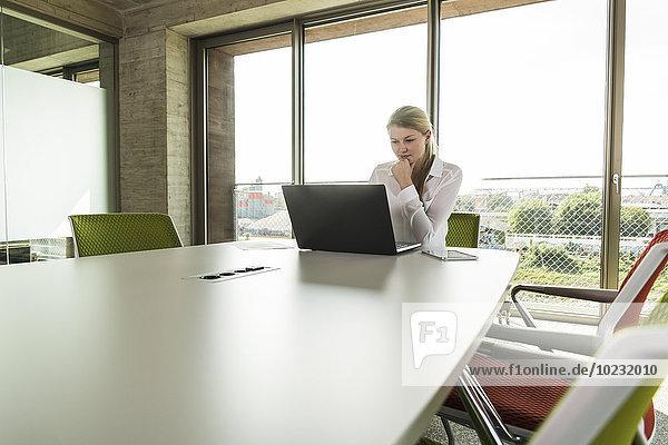 Junge Geschäftsfrau im Konferenzraum mit Laptop