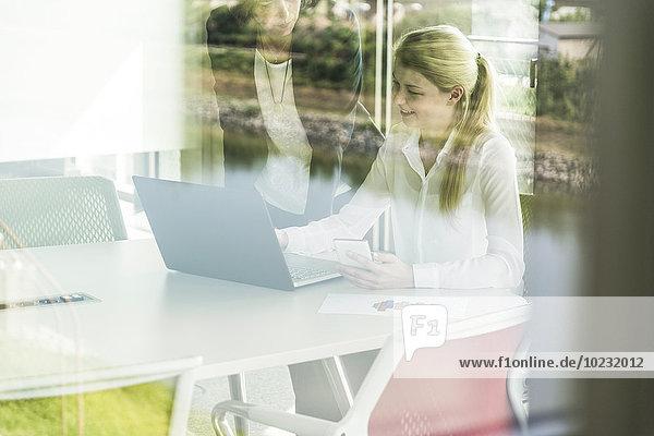 Zwei Geschäftsfrauen im Konferenzraum mit Laptop