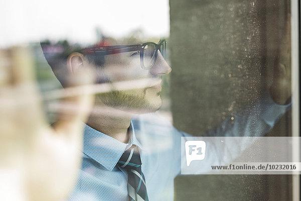 Junger Geschäftsmann mit Blick aus dem Fenster