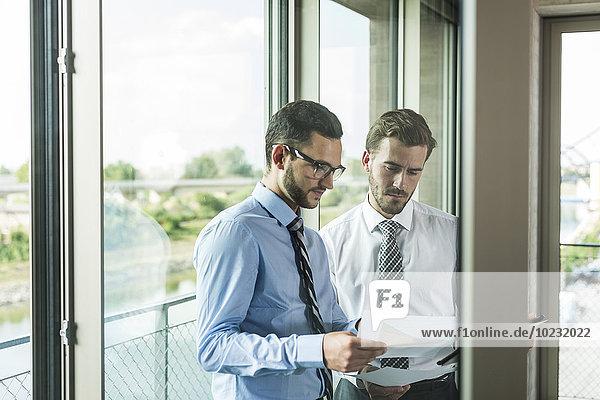 Zwei junge Geschäftsleute schauen sich Dokumente am Fenster an