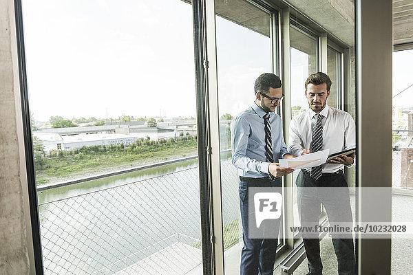 Zwei junge Geschäftsleute diskutieren am Fenster über Dokumente