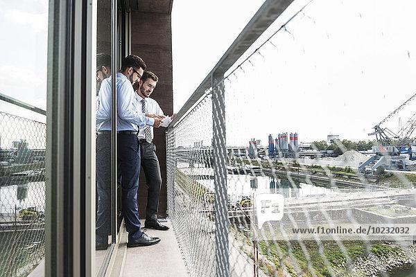 Zwei junge Geschäftsleute diskutieren über Dokumente auf dem Balkon