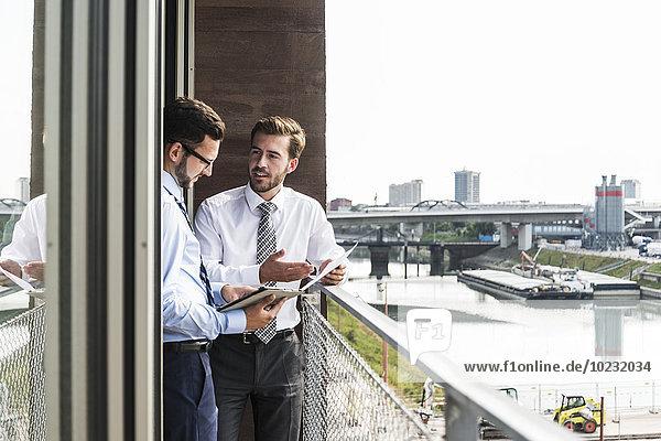 Zwei junge Geschäftsleute mit Dokumenten und digitalem Tablett diskutieren auf dem Balkon