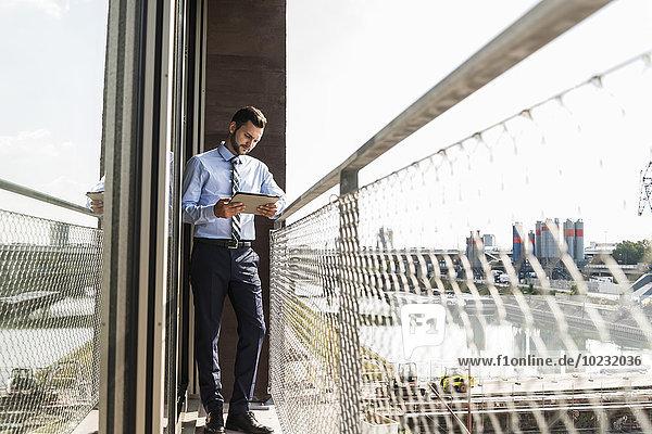 Junger Geschäftsmann auf dem Balkon stehend mit Blick auf digitales Tablett