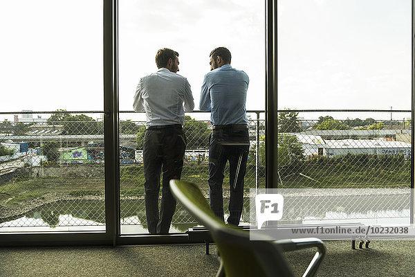 Zwei junge Geschäftsleute  die auf dem Balkon stehen und reden.