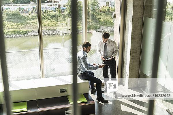 Zwei junge Geschäftsleute auf der Suche nach Dokument und digitalem Tablett