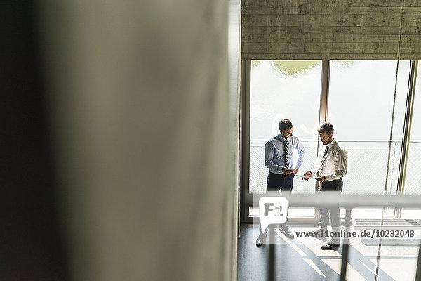 Zwei junge Geschäftsleute diskutieren über Dokumente